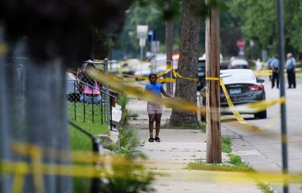 A girl jumps rope outside a home along Bryant Avenue North near the scene of an officer-involved shooting Saturday in Minneapolis.