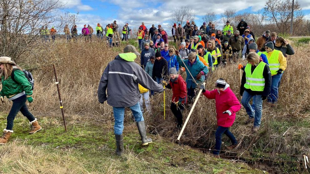 Volunteers cross a creek and barbed wire near Barron, Wis., Oct. 23, 2018, on their way to a ground search for 13-year-old Jayme Closs who was discovered missing Oct. 15 after her parents were found fatally shot at their home. The search for Closs was expanded Oct. 23, with as many as 2,000 volunteers expected to take part in a search of the area.