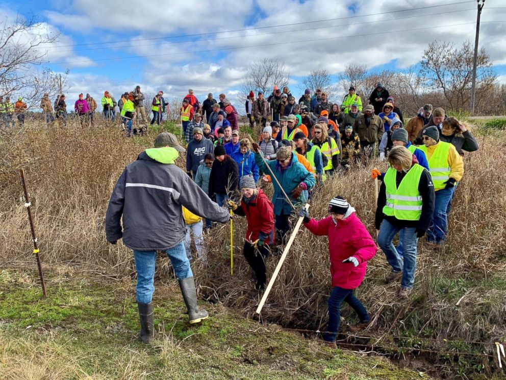 PHOTO: Volunteers cross a creek and barbed wire near Barron, Wis., Oct. 23, 2018, on their way to a ground search for 13-year-old Jayme Closs who was discovered missing Oct. 15 after her parents were found fatally shot at their home.