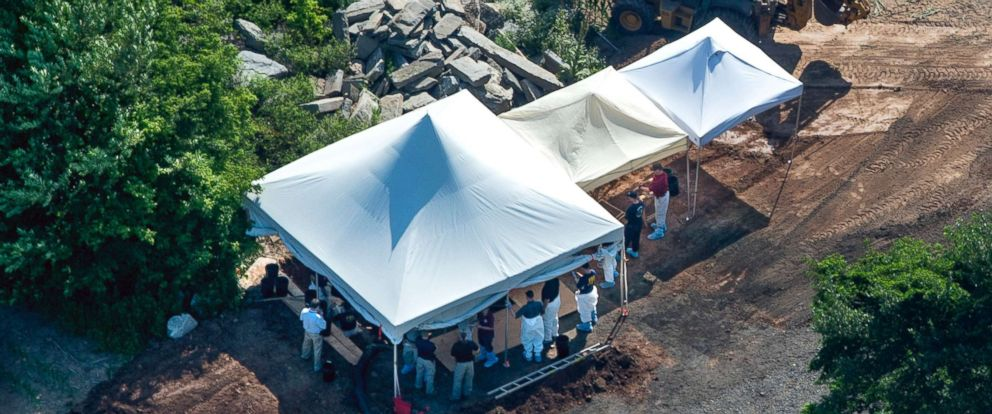 PHOTO: Investigators gather under tents as they search a property, July 12, 2017, in Solebury, Pa., for four missing young Pennsylvania men.