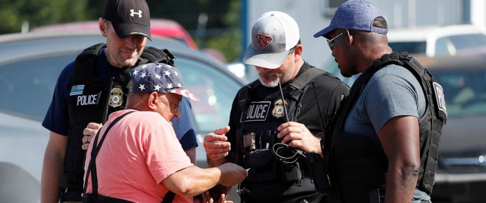 PHOTO: Domingo Candelaria, a registered immigrant, shows federal agents his identification as he prepares to leave the Koch Foods Inc., plant in Morton, Miss., following a raid by U.S. immigration officials, Wednesday, Aug. 7, 2019.