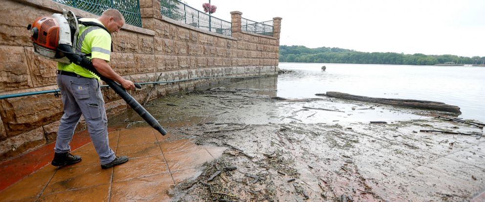 PHOTO: In this Wednesday, June 12, 2019 photo, Matt Cooper, with the City of Dubuque, cleans off an area of American Trust Rivers Edge Plaza in Dubuque, Iowa, after high water levels of the Mississippi River left large amounts of debris and mud.