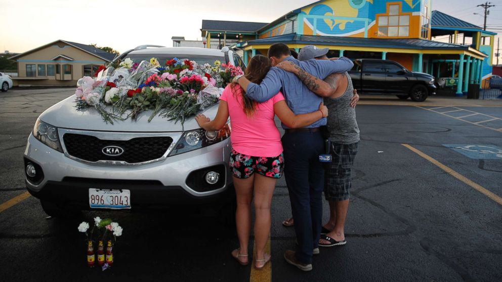 People pray by a car thought to belong to a victim of Thursday's boating accident before a candlelight vigil in the parking lot of Ride the Ducks, July 20, 2018, in Branson, Mo. One of the company's duck boats capsized Thursday night resulting in over a dozen deaths on Table Rock Lake.