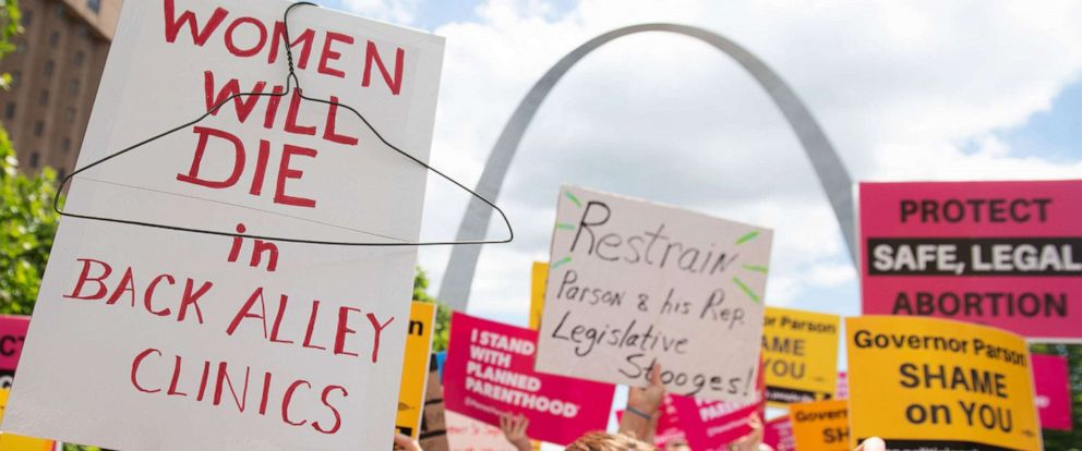 PHOTO: People hold signs as they rally in support of Planned Parenthood and to protest a state decision that would effectively halt abortions by revoking the centers license to perform the procedure, near the Gateway Arch in St. Louis, May 30, 2019.