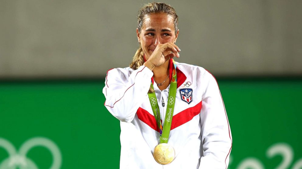Gold medalist Monica Puig of Puerto Rico reacts during the medal ceremony for the Women's Singles Gold Medal Match on Day 8 of the Rio 2016 Olympic Games at the Olympic Tennis Centre, Aug. 13, 2016, in Rio de Janeiro, Brazil.