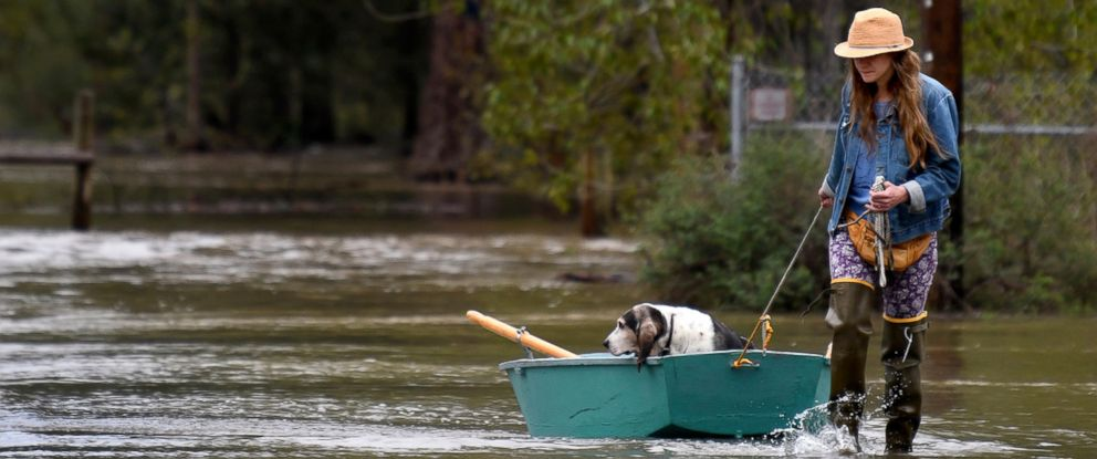 Katie Condon ferries her 13-year-old basset hound, Fran, for a respite from the floodwater surrounding her home at the north end of Tower Street on the outskirts of Missoula, Mont., Monday, May 7, 2018.