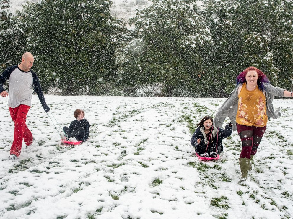 PHOTO: From left, Tommy Little, Cody Little, Kyndra Neal and Tanya Little sled down a hill in Missoula, Mont., Sept. 29, 2019 after snow in an early winter storm.