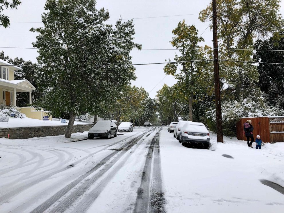 PHOTO: Pedestrians make their way along a snow covered street lined with trees that still have their leaves during a fall snowstorm in Helena, Mont., Sept. 29, 2019.