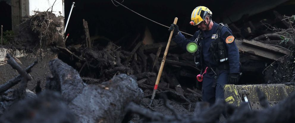 PHOTO: A Los Angeles County urban search and rescue worker searches a pile of debris for victims of a mudslide, Jan. 11, 2018 in Montecito, Calif.