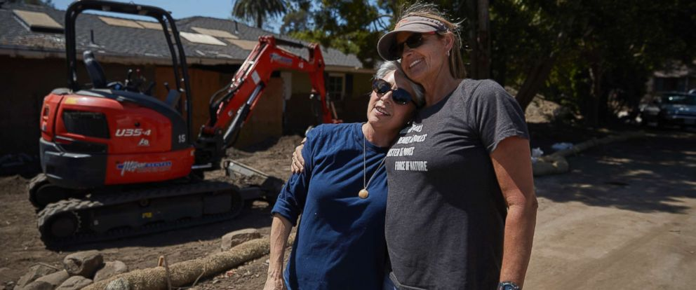 PHOTO: Mudslide survivor Mari Mitchel, left, is hugged by contractor Ann Burgard, who found Mitchels jewelry, outside her home that was heavily damaged by mudslides, in Montecito, Calif., April 11, 2018.