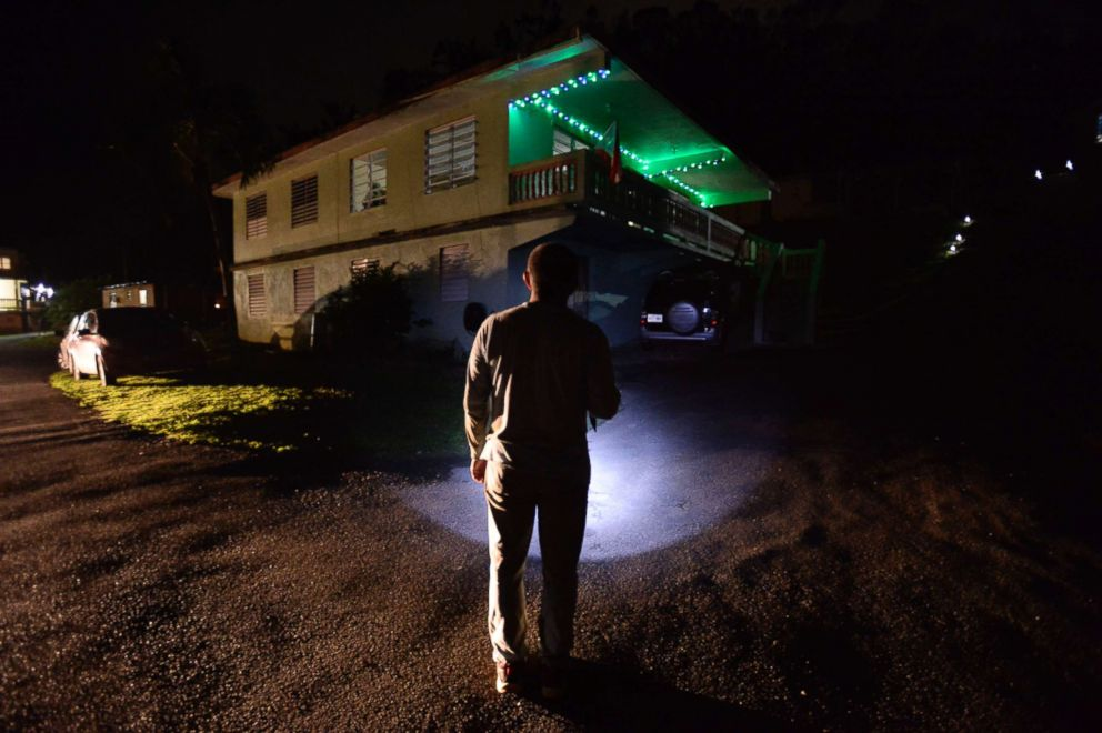 PHOTO: Fifty-six year old Jose Luis Gonzalez lights his path with a lantern on a street in Morovis, Puerto Rico, Dec. 21, 2017. Speaking about the flashbacks that he suffers, Every time I close my eyes I see chaos...I still hear the screams in my head.