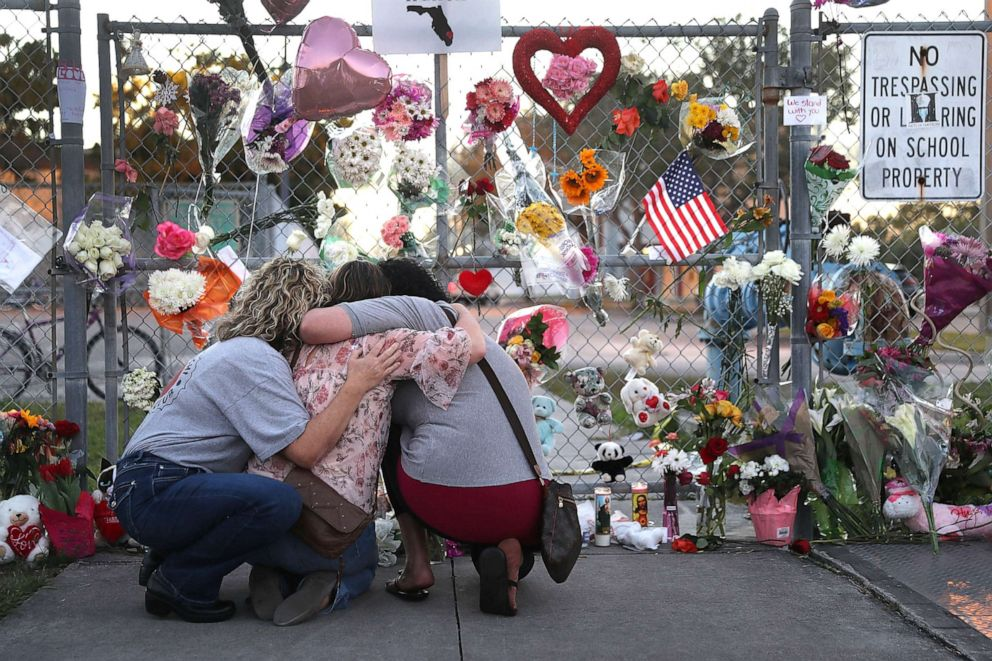 PHOTO:Shari Unger, Melissa Goldsmith and Giulianna Cerbono (L-R) hug each other as they visit a makeshift memorial setup in front of Marjory Stoneman Douglas High School, Feb. 18, 2018, in Parkland, Fla.