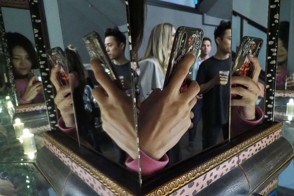 PHOTO: The hand of a visitor taking a photo with a cell phone is reflected in mirrors at the Museum of Selfies, in Glendale, Calif., March 29, 2018.