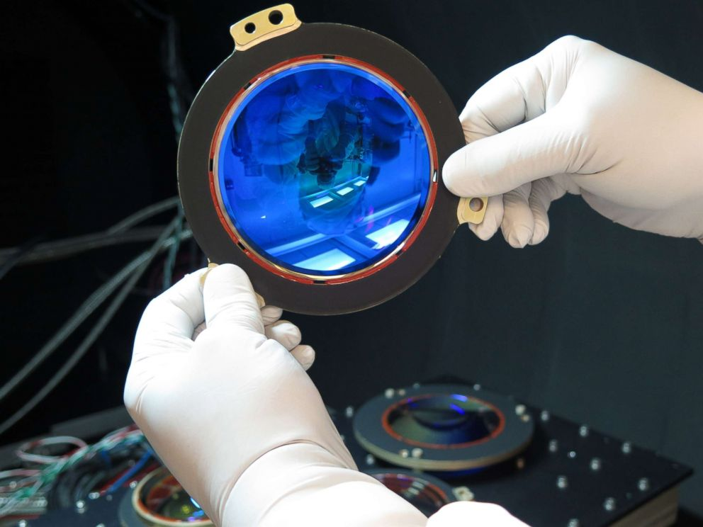 PHOTO: A photo released in 2017 shows an engineer preparing a lens from the TESS satellite for testing.