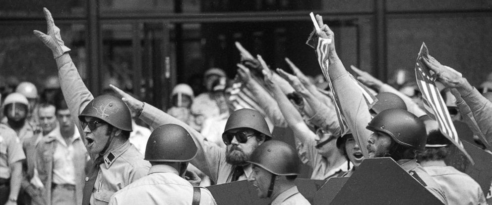 PHOTO: Nazi leader Frank Collin, pictured center, with the swastika armband leads helmeted members of the National Socialist Party of America give the Fascist salute during a rally in downtown Chicago, June 24, 1978.
