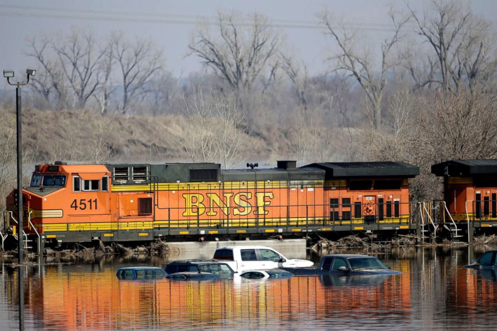 Cars sit in flood waters from the Platte River alongside a BNSF train, in Plattsmouth, Neb., March 17, 2019.