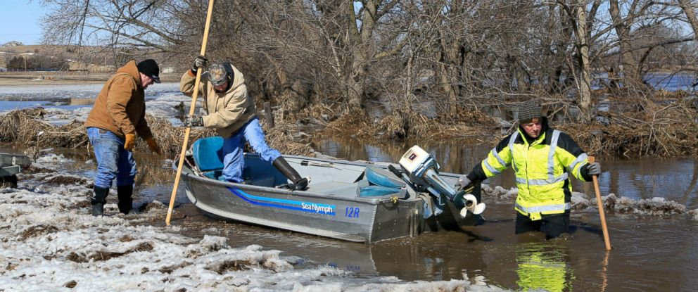 PHOTO: Tom Witke, left, his son Chad, center, and Nick Kenny, launch a boat into the swollen waters of the North Fork of the Elkhorn River, to check on Witkes flooded property, in Norfolk, Neb., Friday, March 15, 2019.