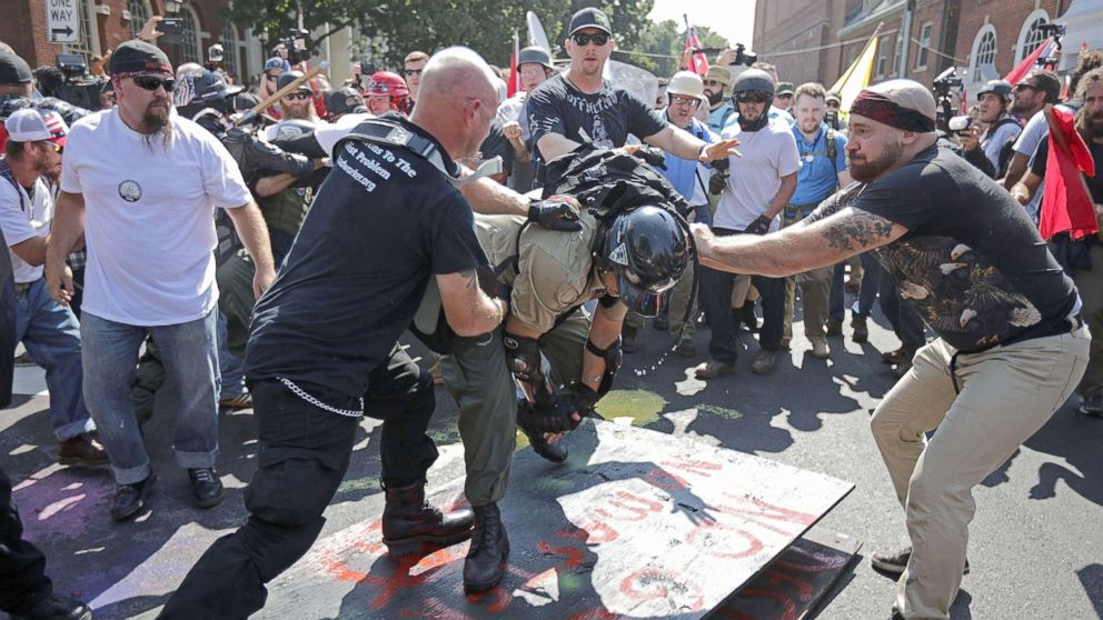 """White nationalists, neo-Nazis, the KKK and members of the """"alt-right"""" attack each other as a counter protester (R) intervenes during the melee outside Emancipation Park during the Unite the Right rally, Aug. 12, 2017, in Charlottesville, Va."""
