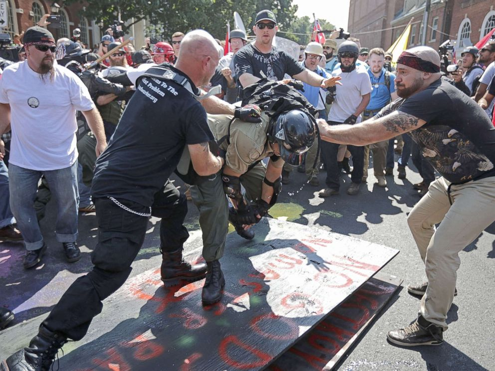 PHOTO: White nationalists, neo-Nazis, the KKK and members of the alt-right attack each other as a counter protester (R) intervenes during the melee outside Emancipation Park during the Unite the Right rally, Aug. 12, 2017, in Charlottesville, Va.