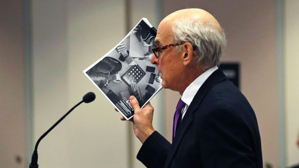 """Attorney Steven M. Gordon, who represents lottery winner """"Jane Doe"""", holds up an annual report from the New Hampshire Lottery during a hearing in the Jane Doe v. NH Lottery Commission case at Hillsborough Superior Court in Nashua, N.H., Feb. 13, 2018."""