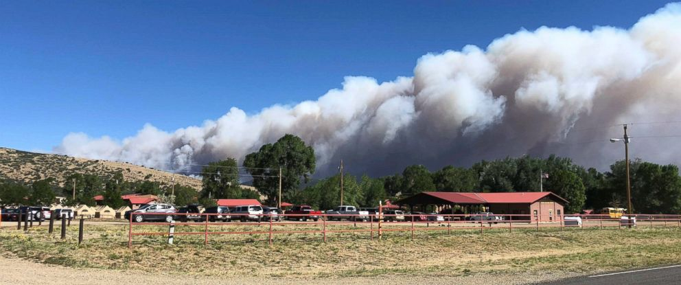 A plume of smoke from a wildfire rises behind Philmont Scout Ranch, Friday, June 1, 2018, near Cimarron, N.M. A wildfire raced across a swath of tinder-dry forest in northeastern New Mexico on Friday.