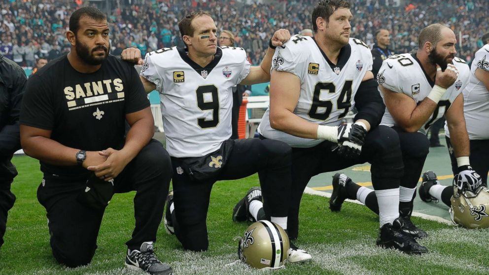 New Orleans Saints quarterback Drew Brees (9) kneels down with teammates before the U.S. national anthem was played ahead of an NFL football game against Miami Dolphins at Wembley Stadium in London, Oct. 1, 2017. Saints players then stood when the anthem was played.