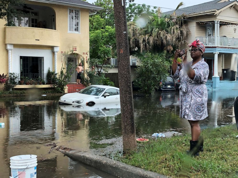PHOTO: A woman stands photographing the scene in a flooded street in New Orleans, July 10, 2019.