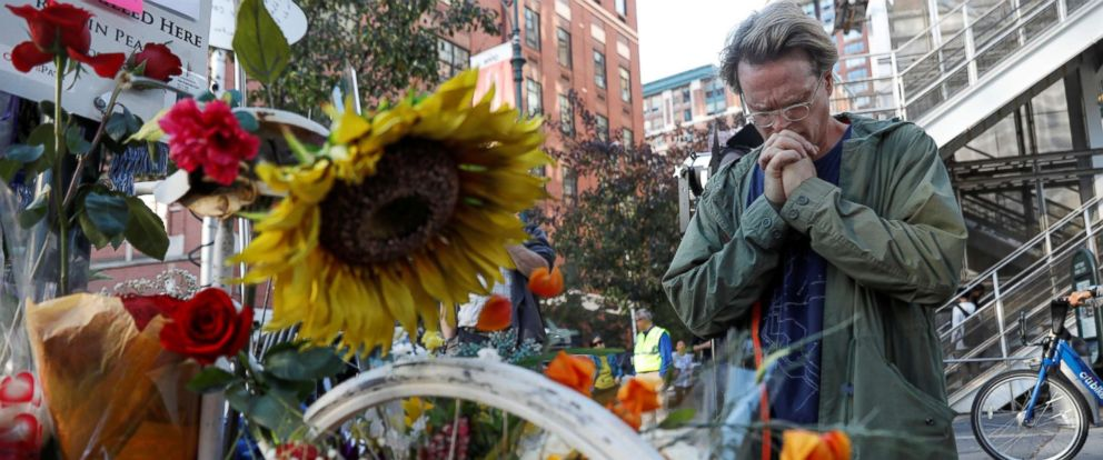 PHOTO: A man prays after laying flowers at an existing roadside memorial, or a ghost bike, that is now used to remember the victims of the Tuesdays attack alongside a bike path at Chambers Street in New York, Nov. 2, 2017.