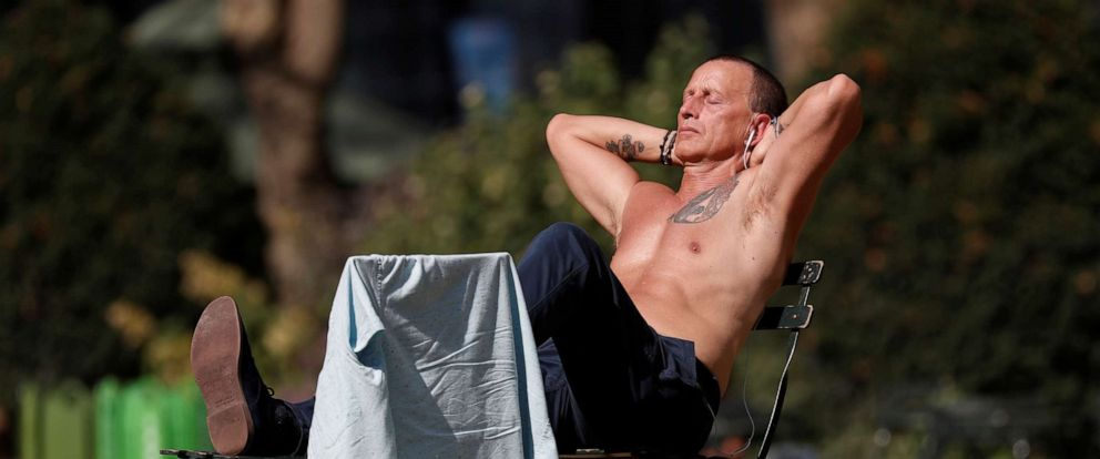 PHOTO: A man lays out in the sun at Bryant Park in New York, October 2, 2019.