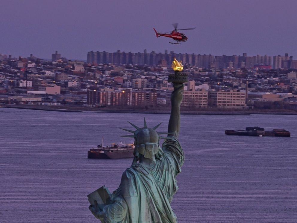 PHOTO: A chartered helicopter that later crashed into New Yorks East River flies past the Statue of Liberty in New York, March 11, 2018.