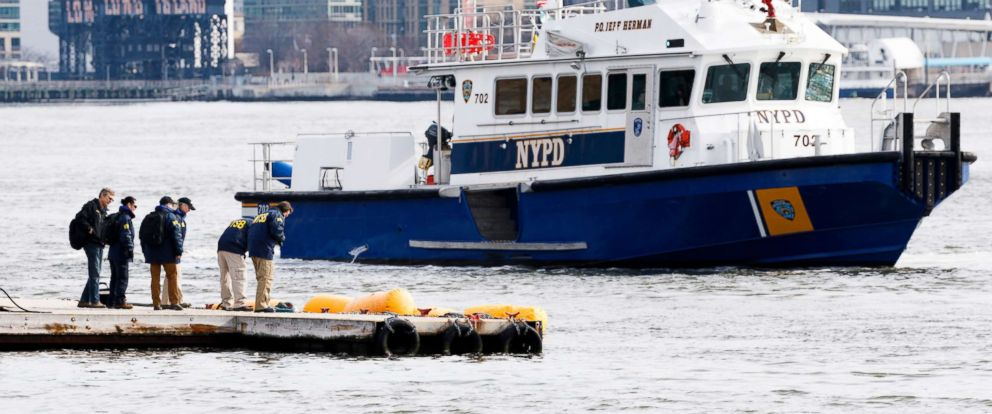 PHOTO: NTSB investigators and a New York City police boat gather near yellow flotation devices attached to the skids of a submerged sightseeing helicopter that crashed a night earlier on the East River in New York, March 12, 2018.