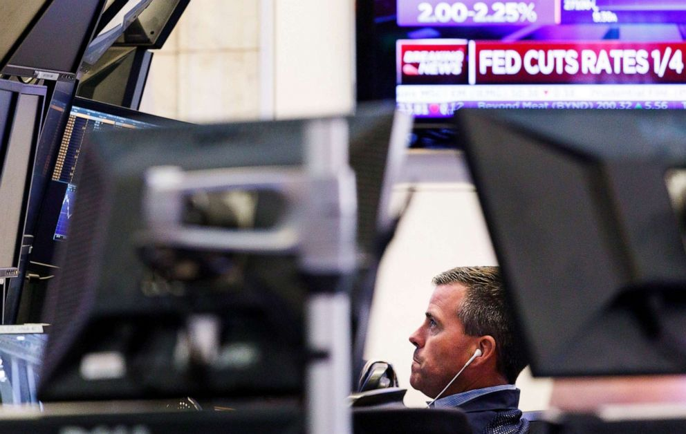 PHOTO: A trader works near a television screen showing news about the United States Federal Reserves decision to lower interest rates by a 1/4 point on the floor of the New York Stock Exchange in New York, July 31, 2019.