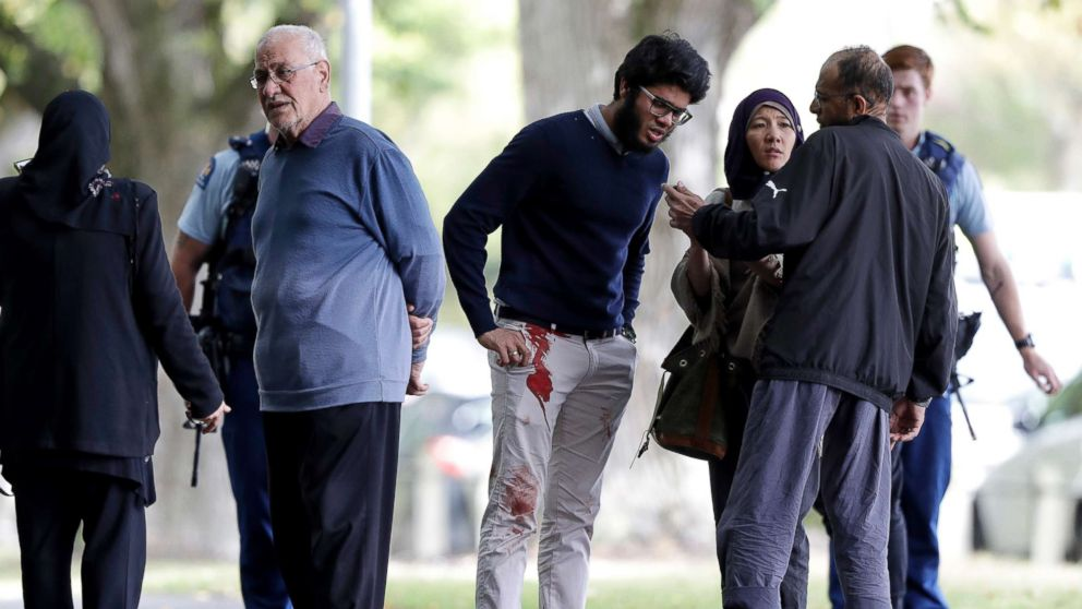 People stand across the road from a mosque in central Christchurch, New Zealand, March 15, 2019.