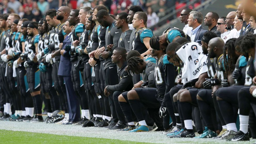Jacksonville Jaguars NFL football players are shown, some standing and some kneeling, during the playing of the national anthem at Wembley Stadium in London.