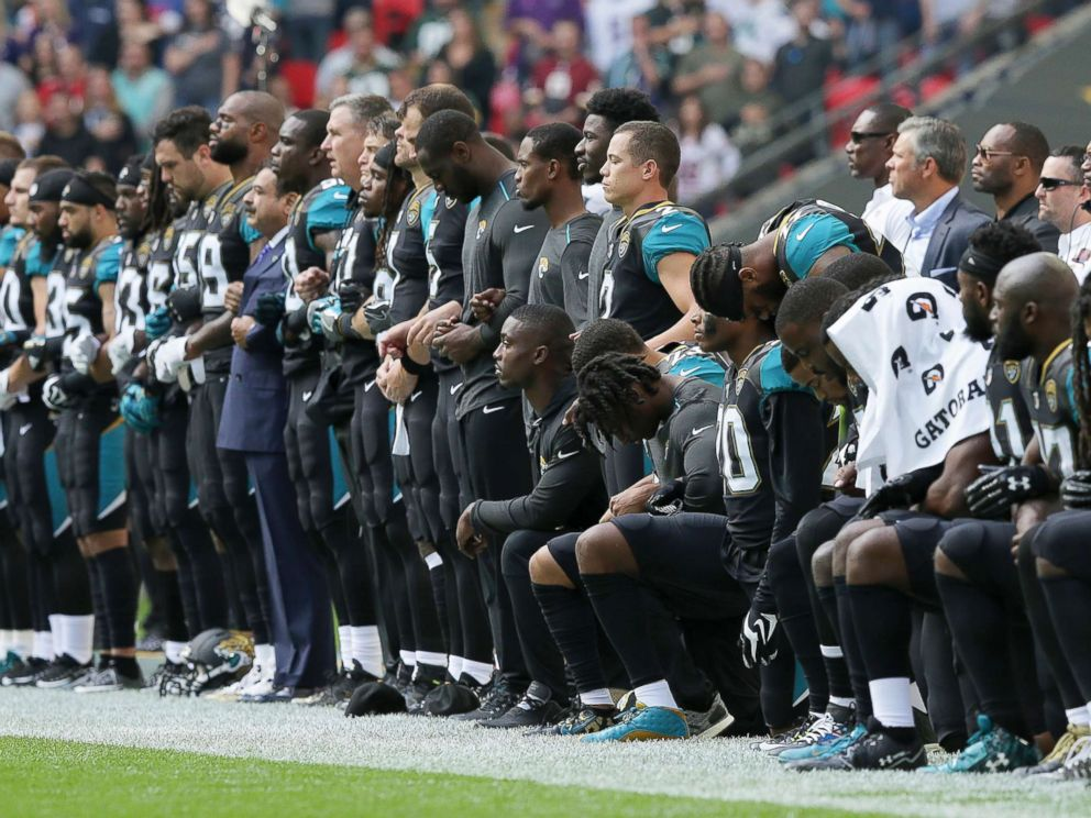 PHOTO: Jacksonville Jaguars NFL football players are shown, some standing and some kneeling, during the playing of the national anthem at Wembley Stadium in London.