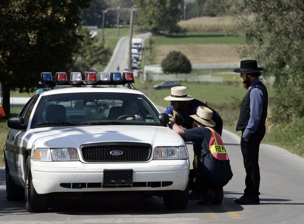 PHOTO: Amish men speak with a police officer on a road leading to the one-room West Nickel Mines Amish School, Oct. 3, 2006, in the town of Nickel Mines, Penn. a day after a shooting at the school left three girls dead.