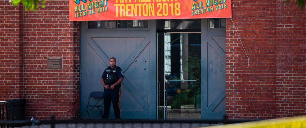 PHOTO: A Police officer stands in front as other officers inspect the crime scene at the Roebling Market, June 17, 2018, the morning after a shooting at an all-night art festival injured 20 people and left one person dead in Trenton, New Jersey.