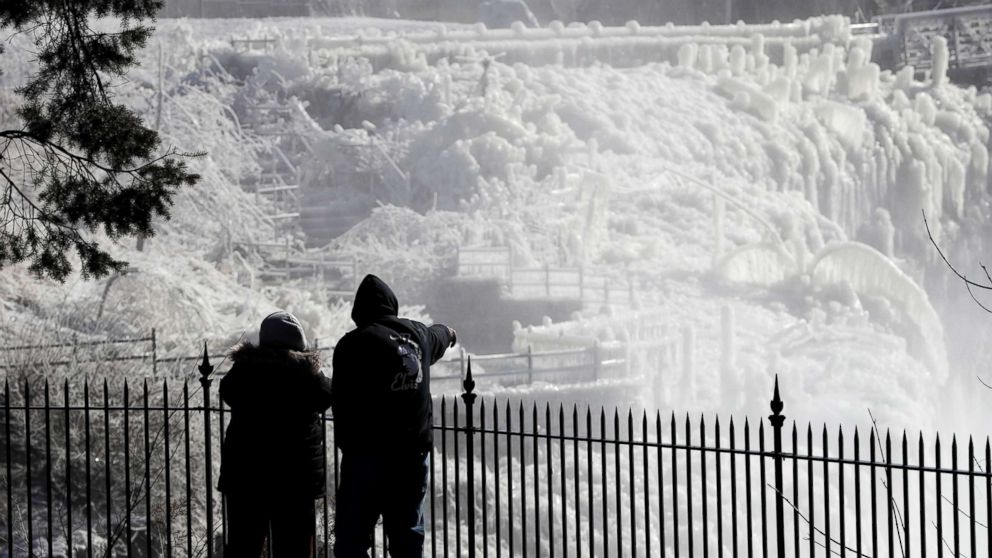 Ice is seen on the side of the Great Falls National Historic Park as a couple takes in the sights during a frigid winter day, Jan. 30, 2019, in Paterson, N.J.