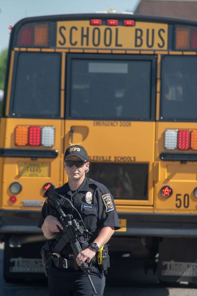 PHOTO: An armed police officers stands on the scene outside Noblesville High School as evacuated middle school students wait on a bus after a shooting at Noblesville West Middle School on May 25, 2018 in Noblesville, Ind.