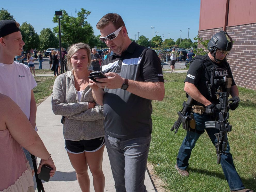 PHOTO: Parents wait while a SWAT officer passes outside Noblesville High School after a shooting at Noblesville West Middle School on May 25, 2018 in Noblesville, Ind.