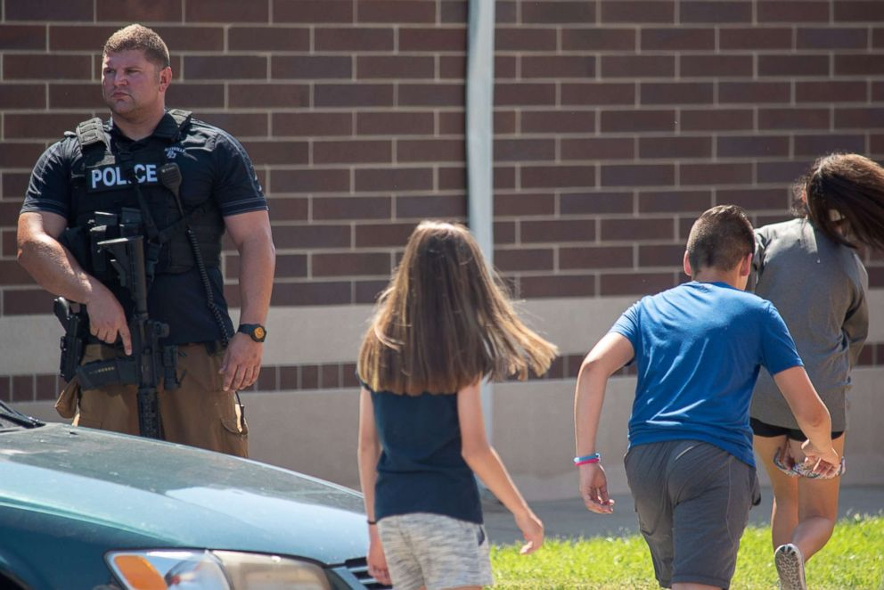 PHOTO: Children File Past An Armed Police Officer Outside Noblesville High  School After A Shooting