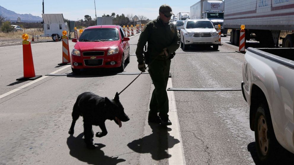 A U.S. Border Patrol agent and drug sniffing German Shepherd prepare to search vehicles for drugs at a checkpoint near the U.S. Mexico border on Feb. 26, 2013 north of Nogales, Ariz.