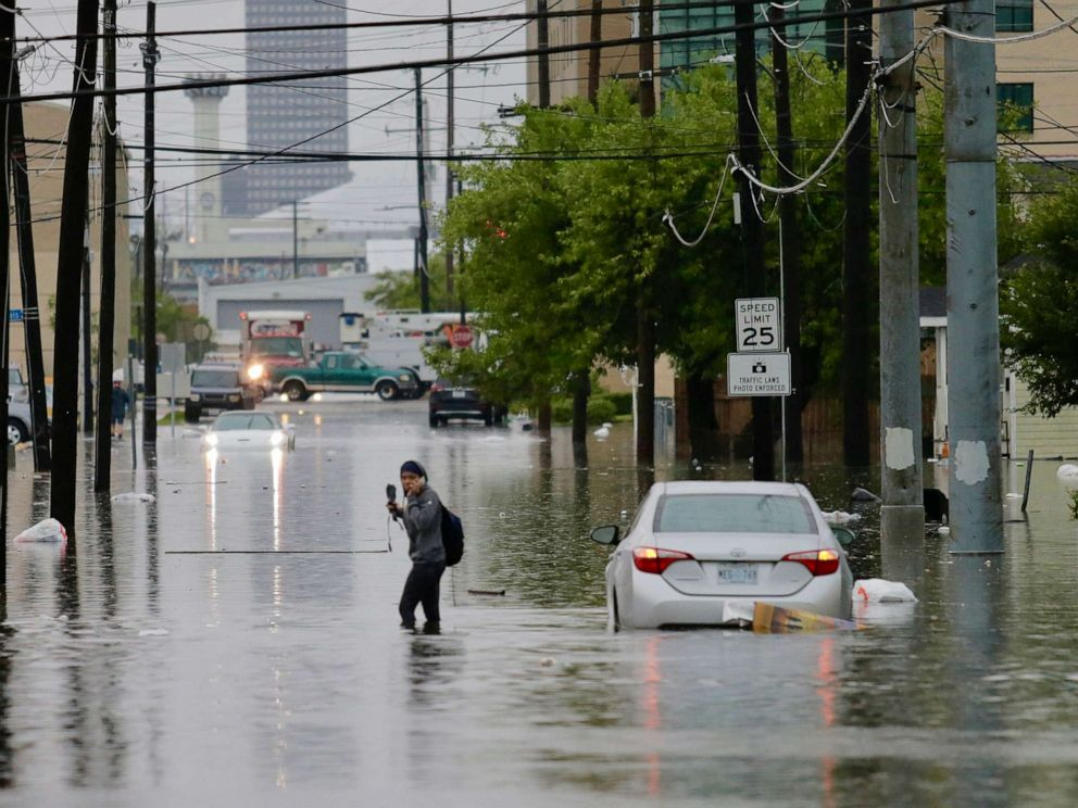 PHOTO: A person crosses a flooded road as heavy rain falls, July 10, 2019, in New Orleans.