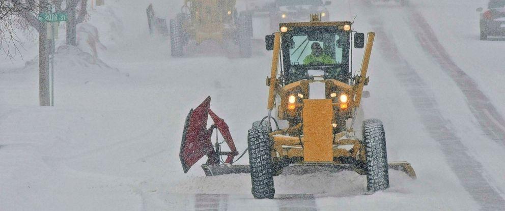 PHOTO: Motor graders plow Rosser Avenue as snow falls, Friday, Jan. 18, 2019, in Bismarck, N.D.