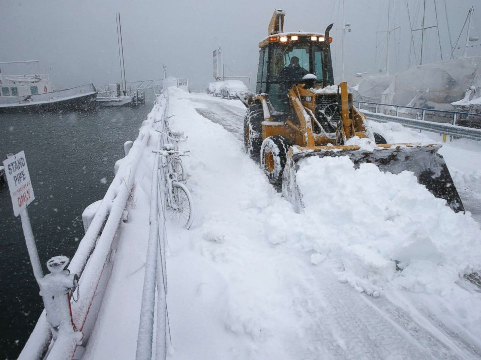 PHOTO: A front end loader clears the pier at the Boston Harbor Shipyard and Marina in Boston, March 13, 2018.