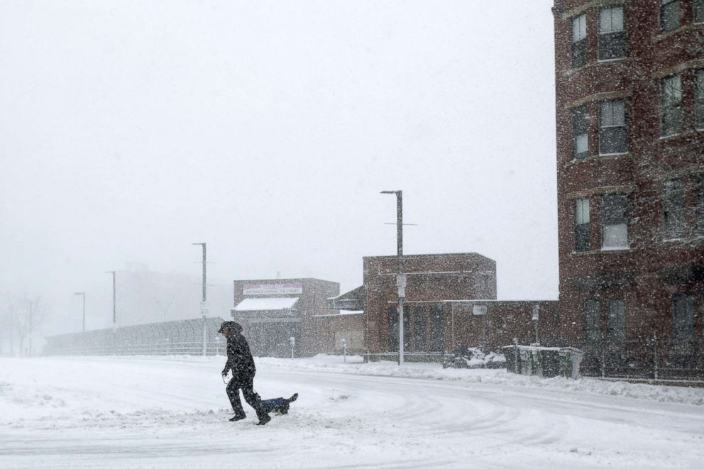 PHOTO: A man crosses a street with his dog against heavy winds and blowing snow as a winter storm bears down, March 13, 2018, in Boston.