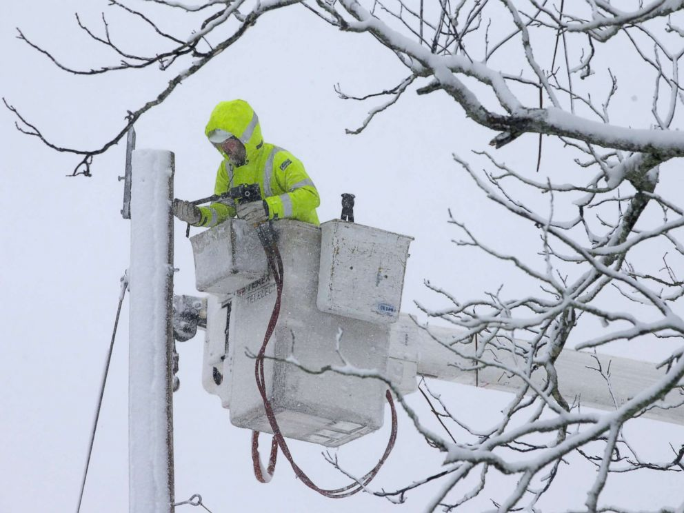 PHOTO: A worker repairs power lines during a winter storm, March 13, 2018, in Norwell, Mass.