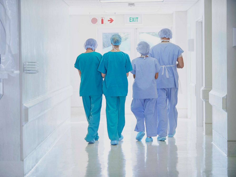 PHOTO: A rear view of four medical staff wearing scrubs is seen in this undated stock photo.