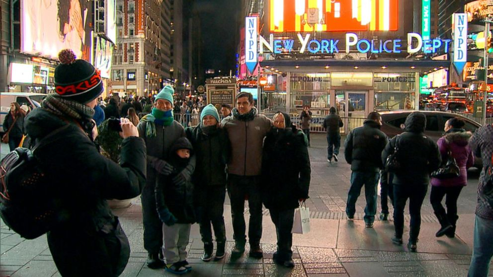 PHOTO: Visitors take a picture in front of the New York Police Department station in Times Square, New York.