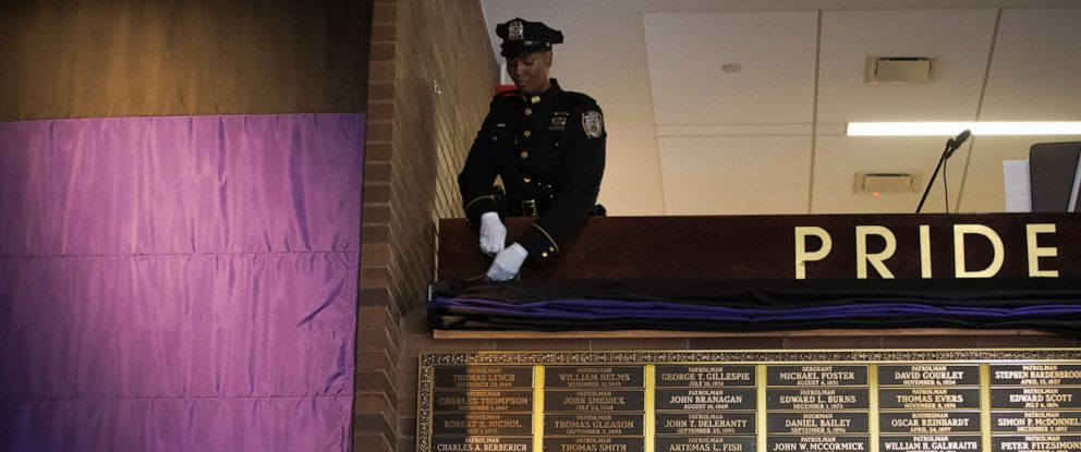 PHOTO: A member of the NYPD Ceremonial Unit unveils new names on the Police Memorial Wall during a ceremony at One Police Plaza, the headquarters of the New York City Police Department, May 4, 2018, in New York.